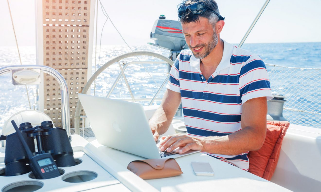 82561184 - man with laptop computer on sailboat